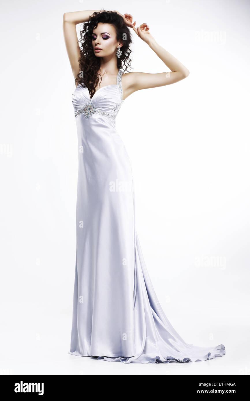 Hermosa dama a la luz de seda vestido sin mangas con la joyería del platino. Sensualidad Imagen De Stock