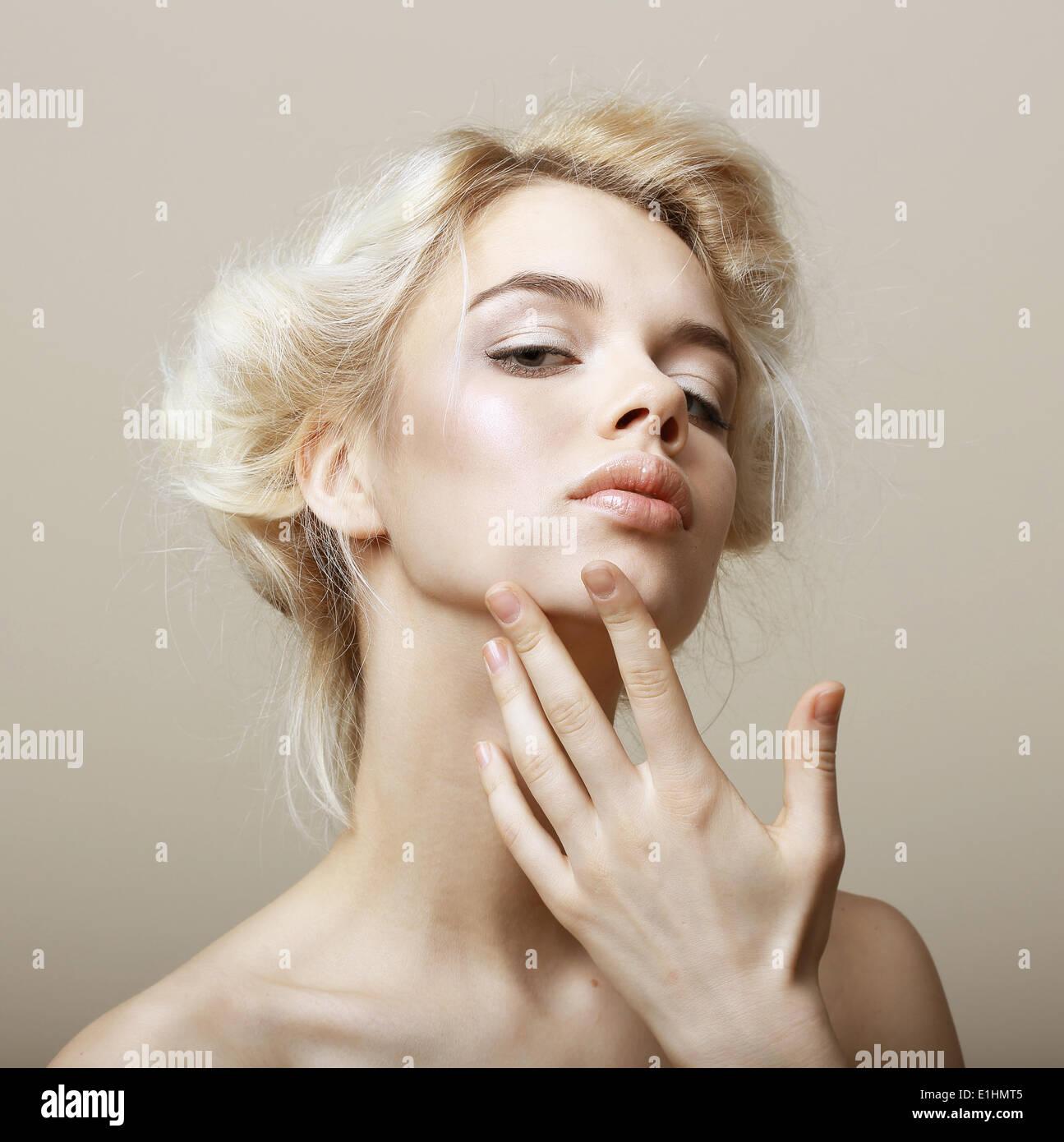 El sentimentalismo. Mujer rubia natural tocando su cara limpia. Mimos. Imagen De Stock