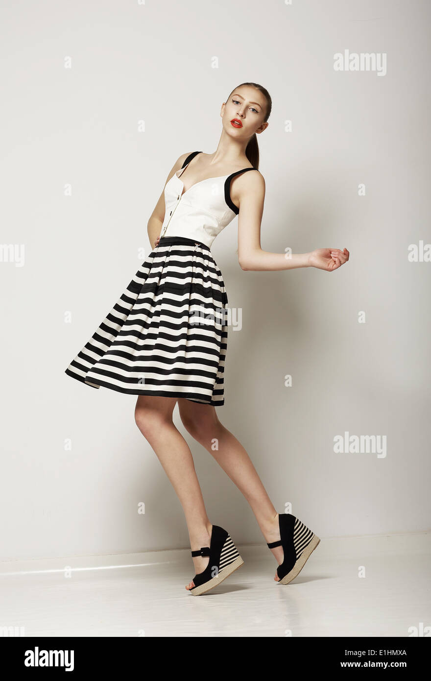 Estilo de moda. Feliz Young Shopper en contraste gris rayas falda. Movimiento Imagen De Stock