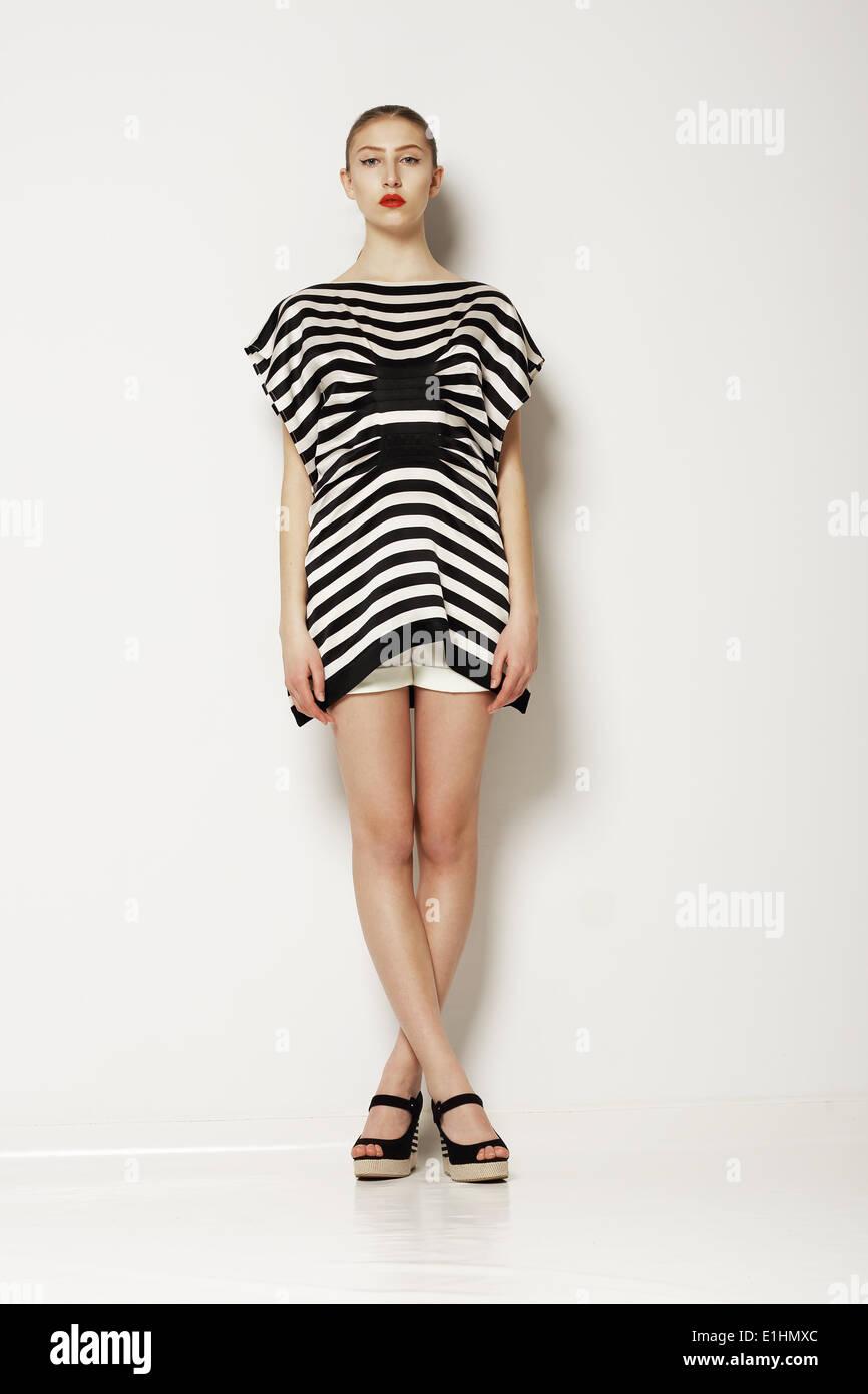 La actitud. Mujer elegante moderno en gris elegante vestido. Las piernas cruzadas Imagen De Stock