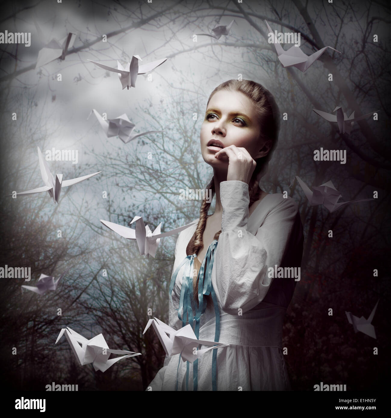 La inspiración. Mujer con origami cisnes blancos volando en oscuro bosque místico Foto de stock