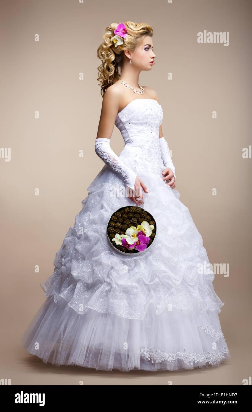 Estilo de la boda. Vestidos de novia vestido blanco y guantes. Bouquet de flores de moda Imagen De Stock