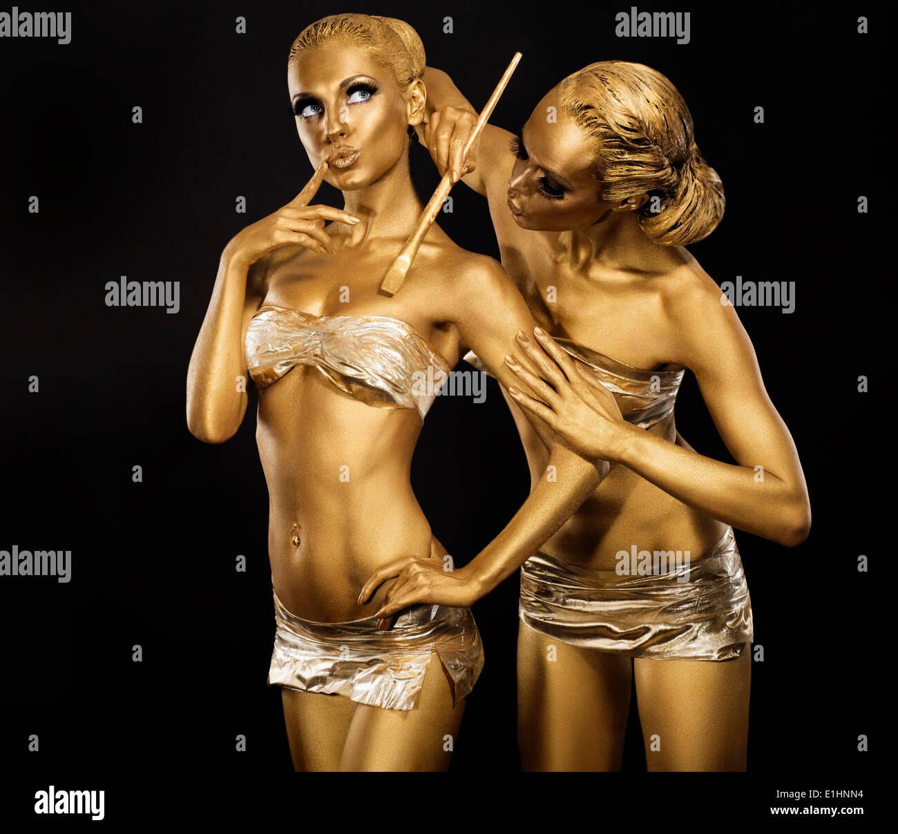 El arte del cuerpo. Mujer pintura Cuerpo con cepillo de la pintura en color dorado. Maquillaje de oro Imagen De Stock