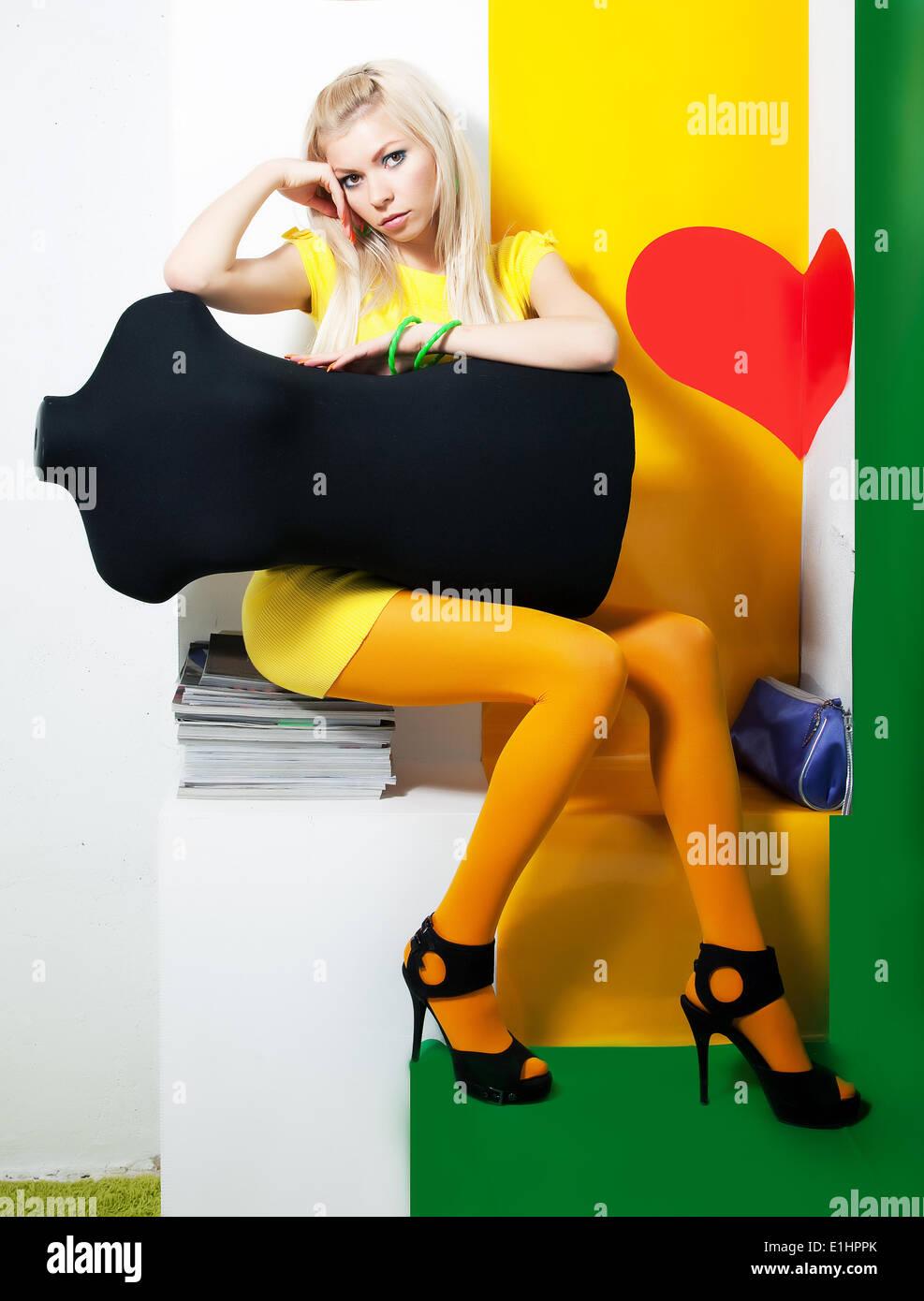 Mujer elegante cabello rubio posando en el estudio con maniquí negro Foto de stock