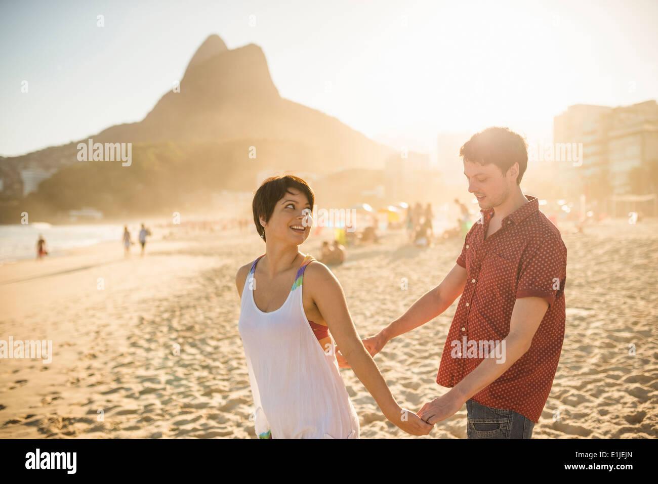 Pareja joven disfrutando del atardecer, la playa de Ipanema, Río de Janeiro, Brasil Imagen De Stock