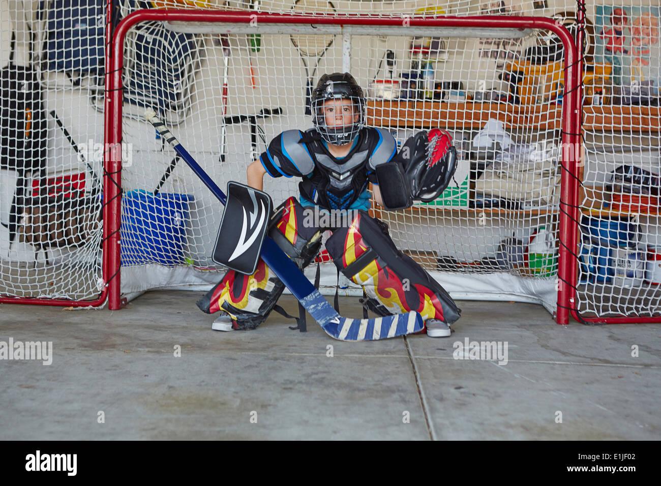 Boy en el hockey gol vistiendo ropa protectora Imagen De Stock