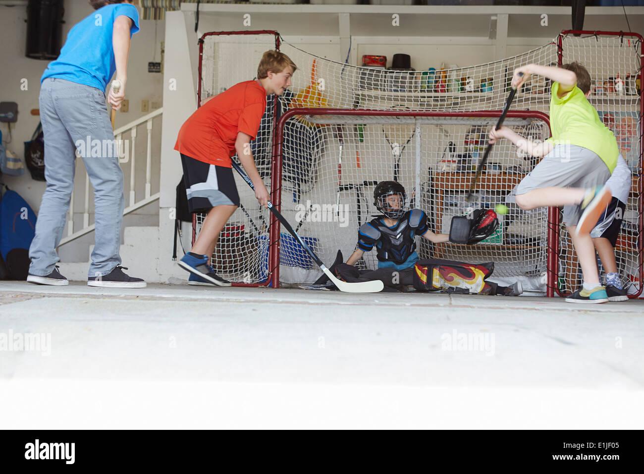 Niños jugando al hockey en el garaje Imagen De Stock