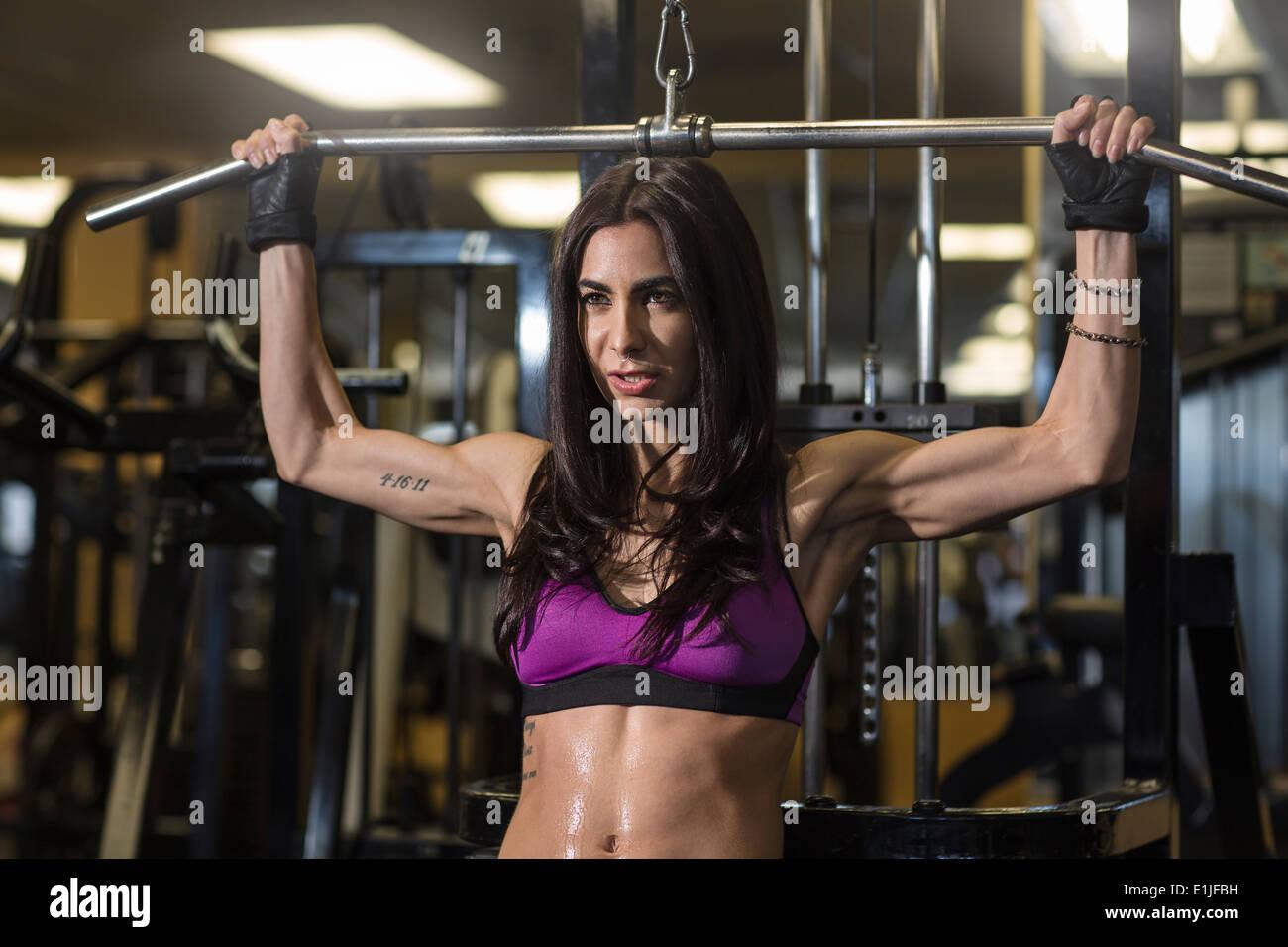 Mitad mujer adulta con la barra en el gimnasio para ejercicios pectorales Imagen De Stock