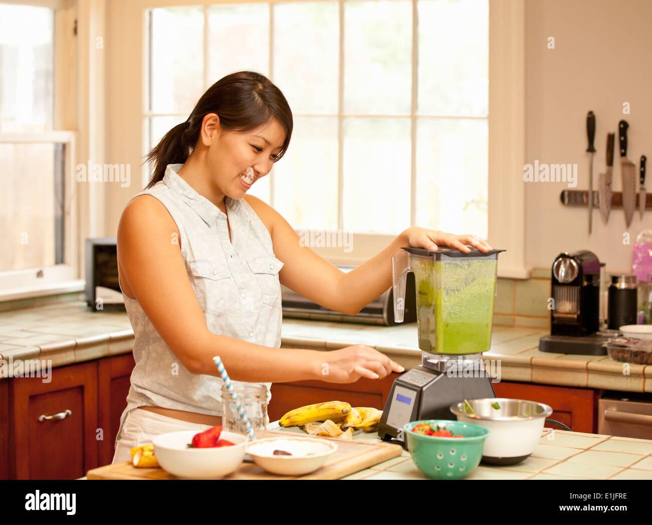 Mujer joven haciendo batido verde en la cocina Imagen De Stock
