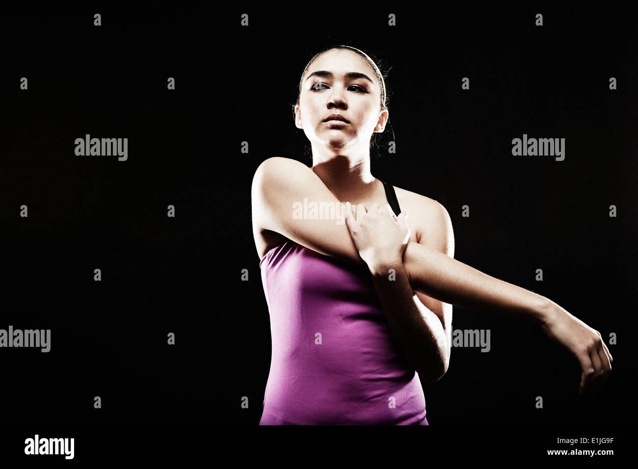 Mujer joven estirando el brazo Imagen De Stock