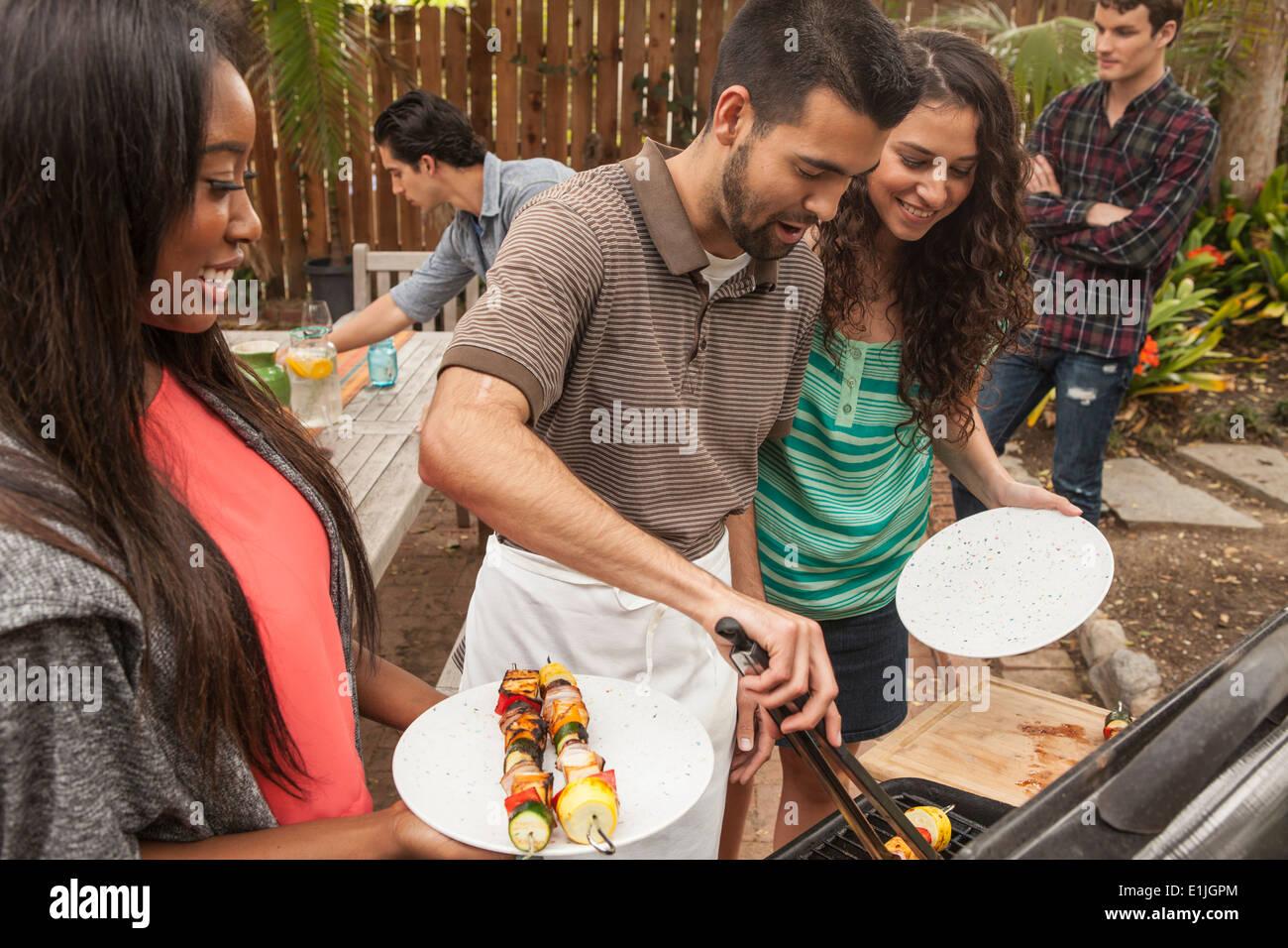 Amigos sentados alrededor de mesa compartiendo comida de barbacoa Imagen De Stock