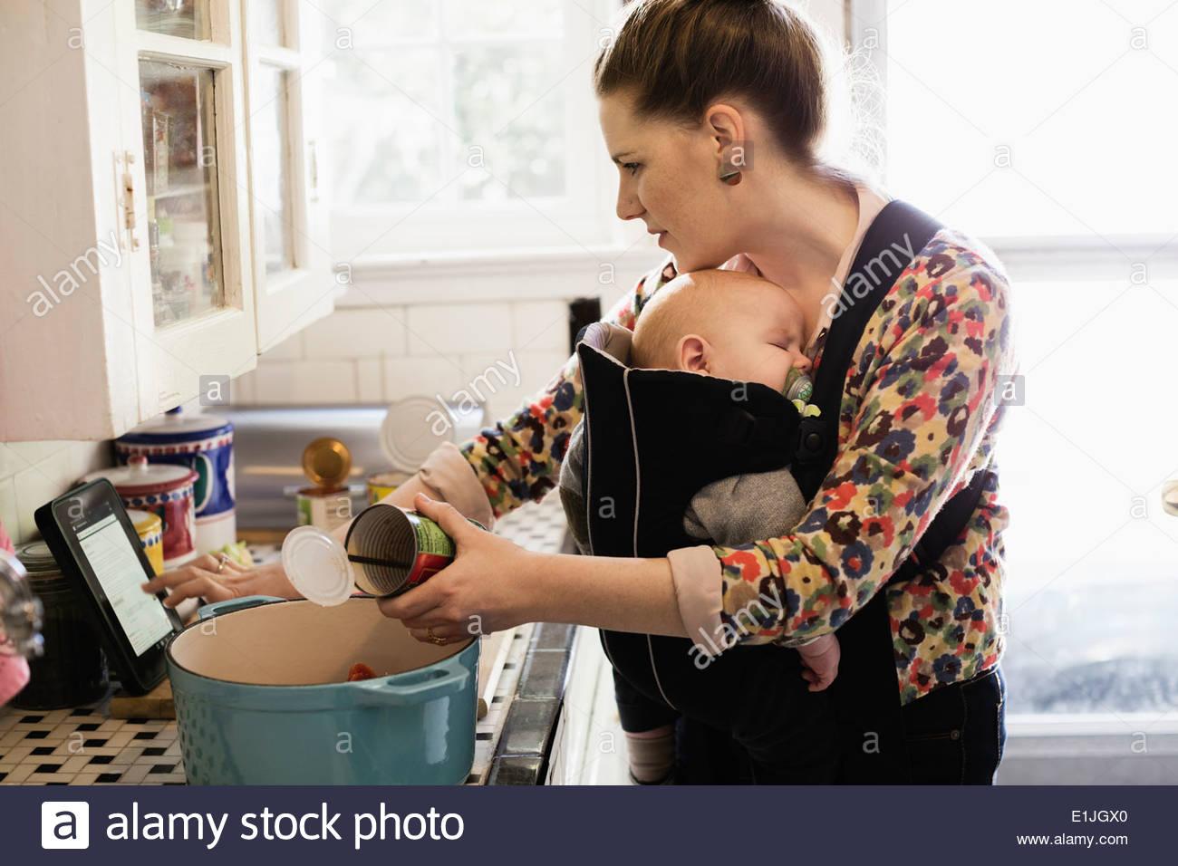 Adulto medio madre con su hijo en cabestrillo preparando la comida en la cocina Imagen De Stock