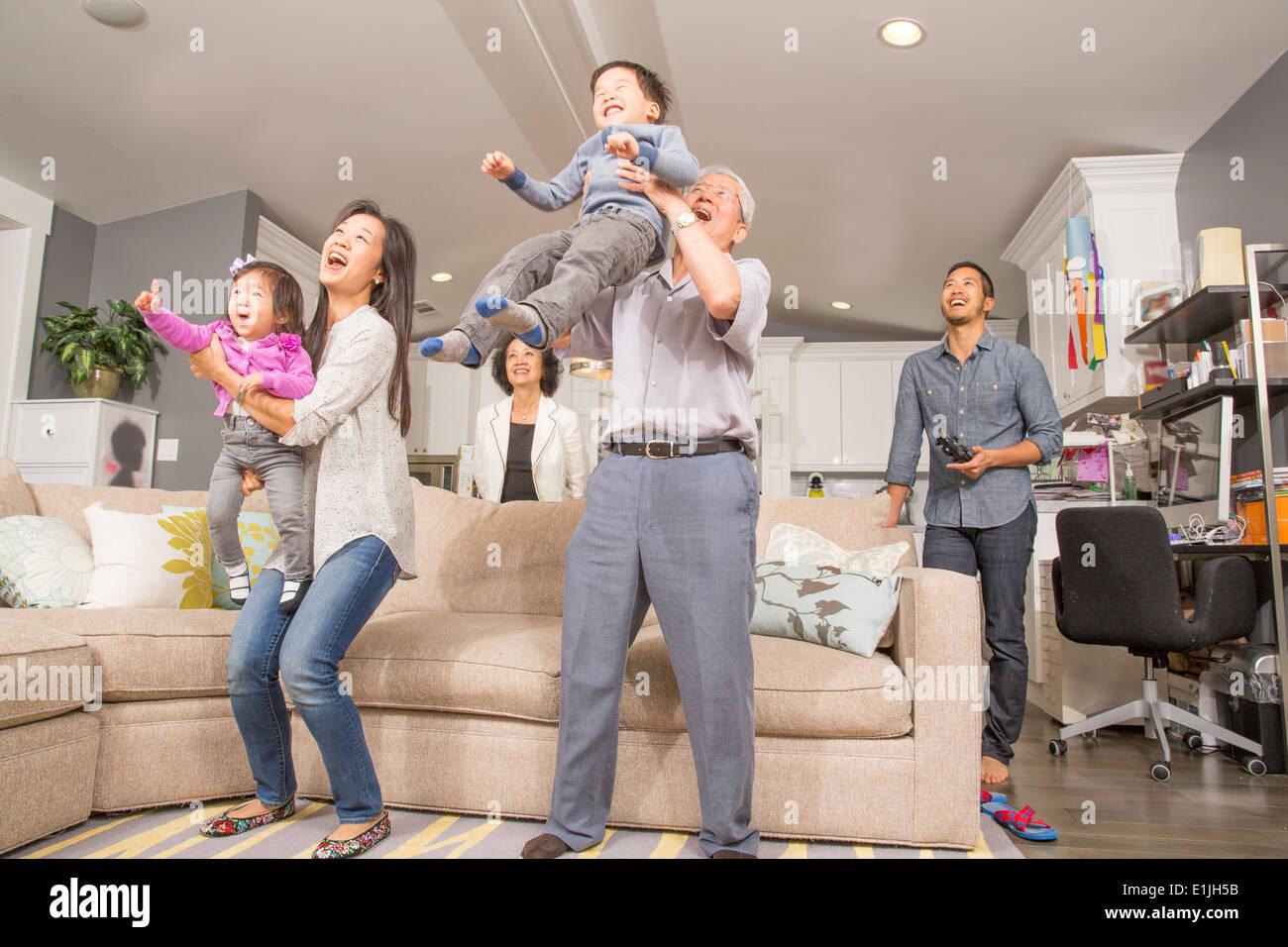 Tres generaciones familia divirtiéndose en salón. Imagen De Stock