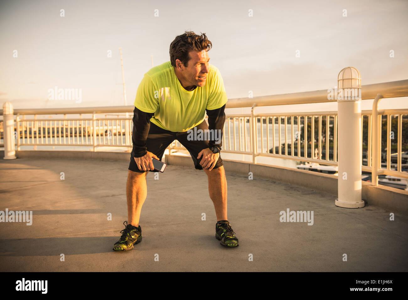 Agotado corredor masculino tomando un descanso Imagen De Stock