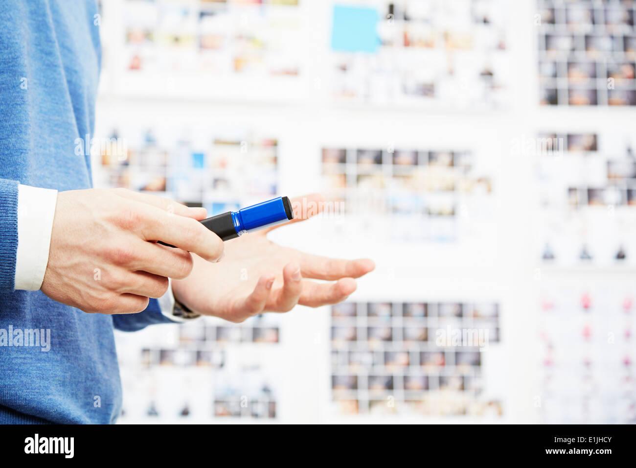 Cerca de joven sosteniendo pen, gesticulando Imagen De Stock