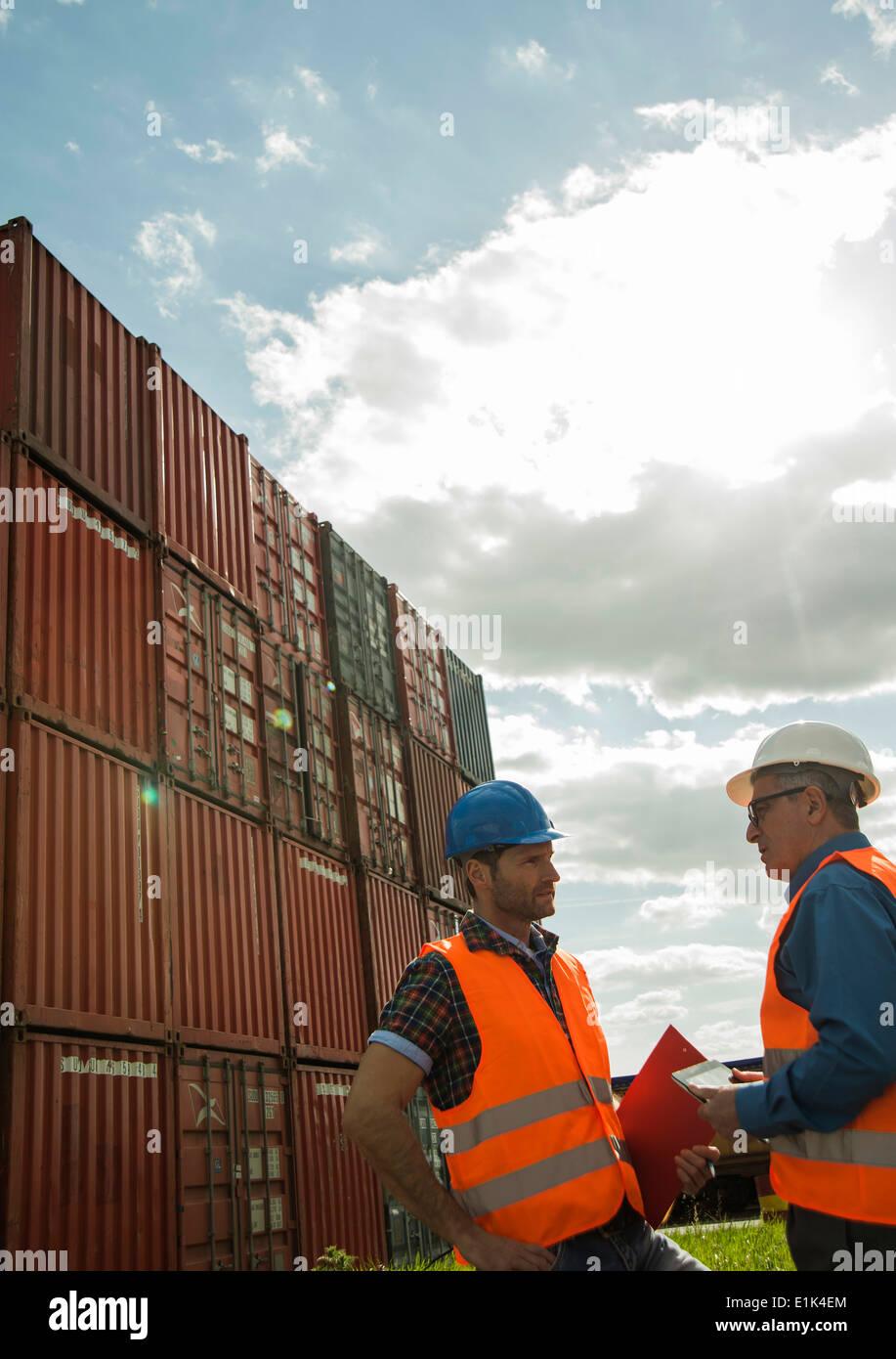 Dos hombres con cascos de seguridad y chalecos reflectantes hablando al puerto de contenedores Foto de stock