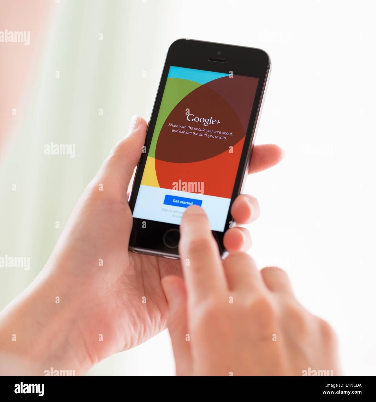 Persona sosteniendo un nuevo Apple iPhone 5S con Google+ aplicación en una pantalla Foto de stock