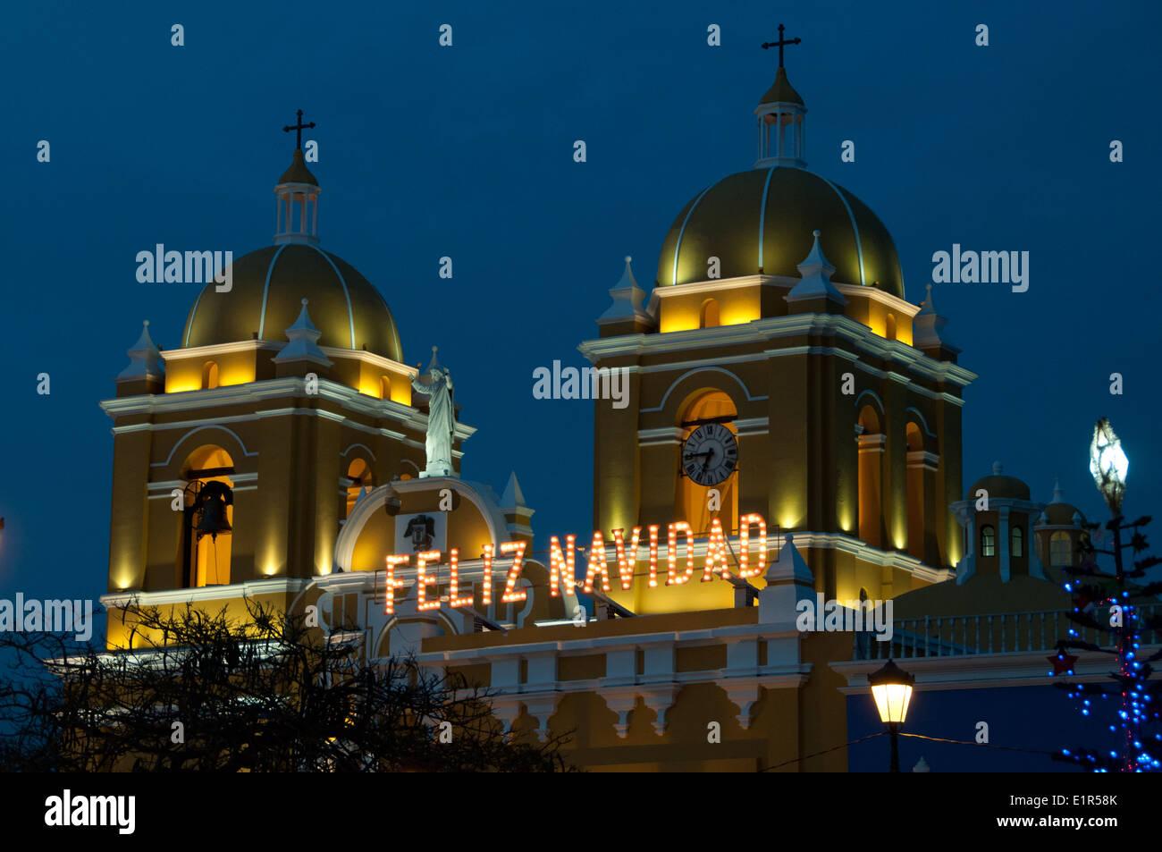 Feliz Navidad Feliz Navidad iluminado con luces a través de las cúpulas de la Catedral, en el centro de Trujillo Peru Imagen De Stock