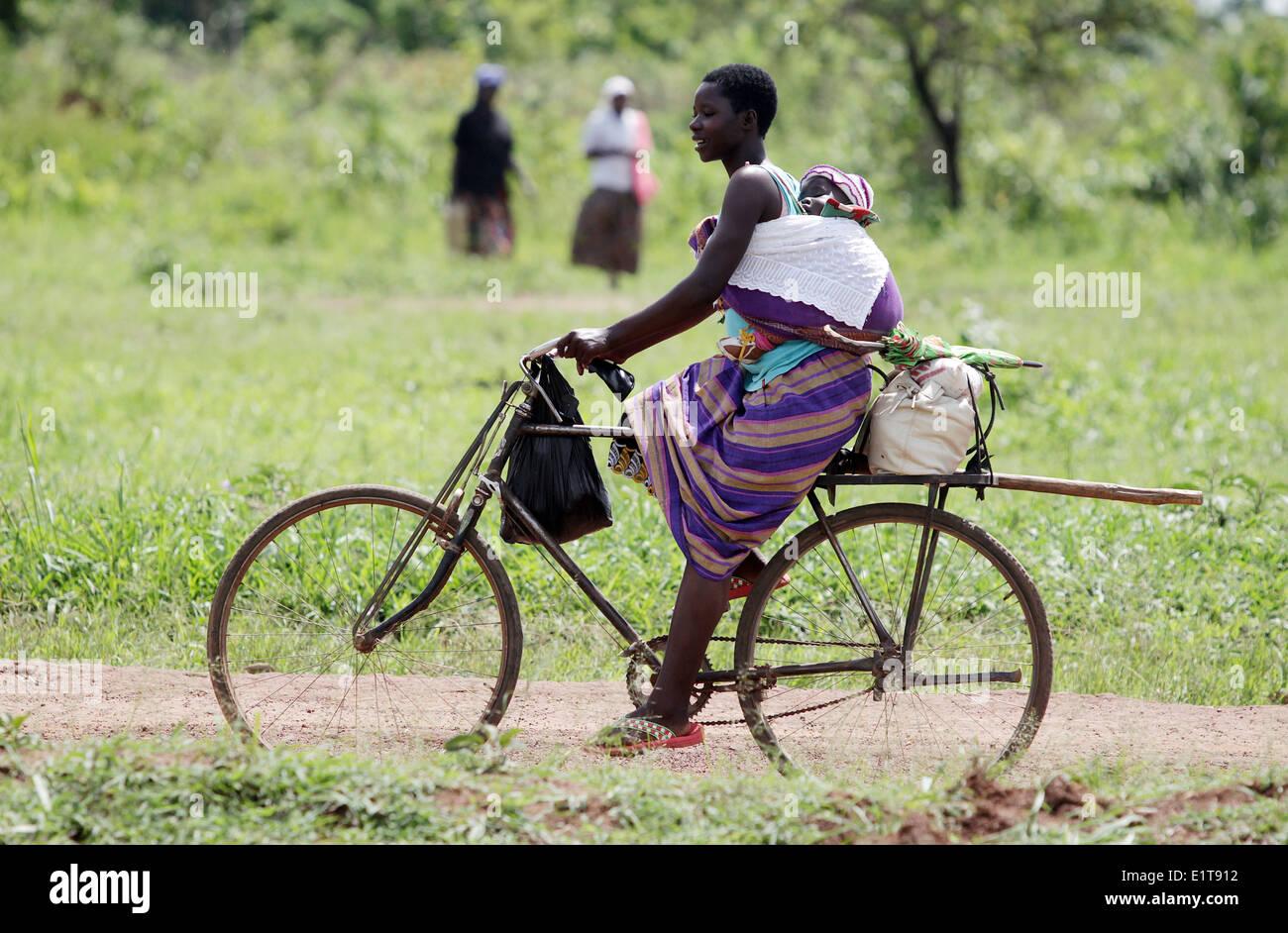 Una madre y su bebé ciclo en la parte rural del distrito de Lira, en el norte de Uganda. Imagen De Stock