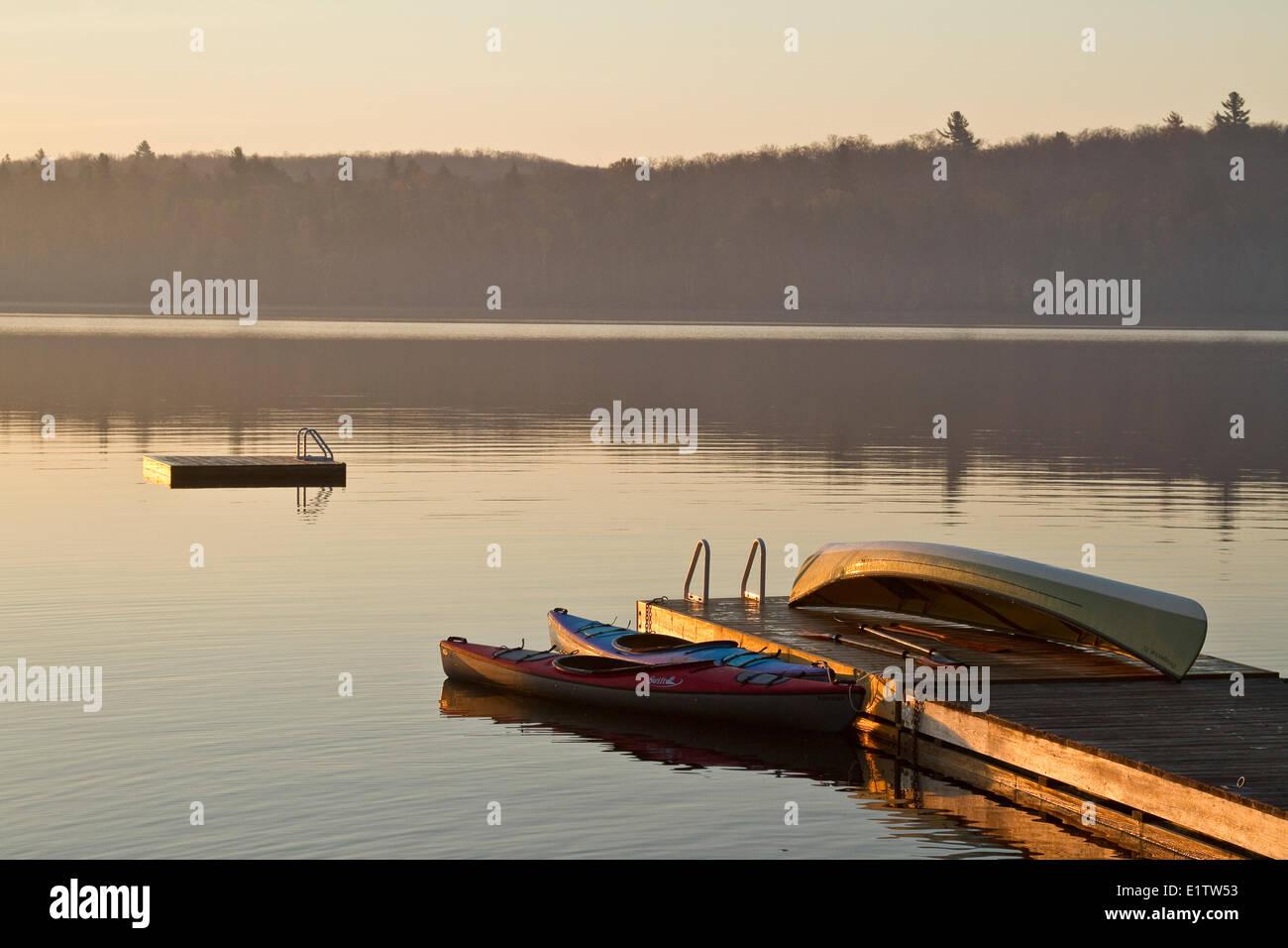 Canoas y kayaks en dock, lago de origen, Algonquin Park, Ontario, Canadá. Foto de stock