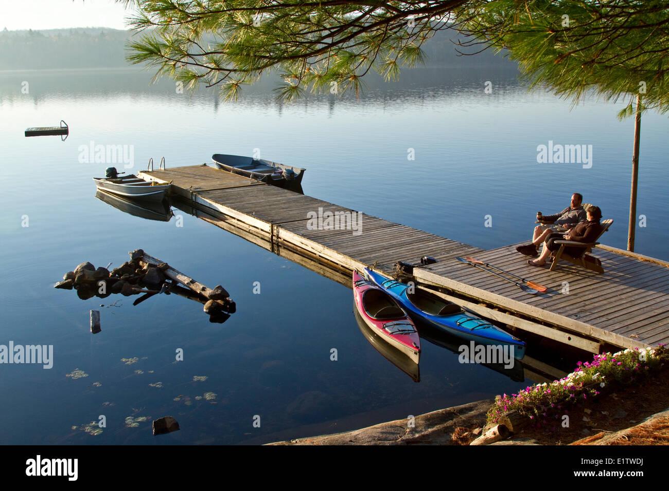Pareja de mediana edad disfrutar mañana tranquila en el muelle cerca de su cabaña de origen, Lago, Parque Algonquin, Foto de stock