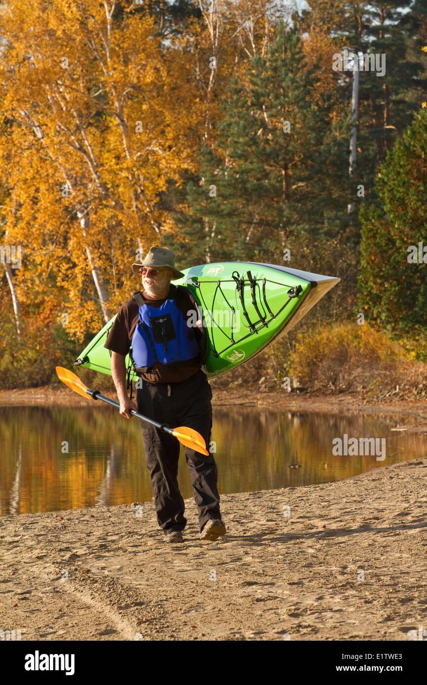 Hombre maduro lleva kayak desde el agua, Oxtongue Lago Muskoka, Ontario, Canadá. Imagen De Stock