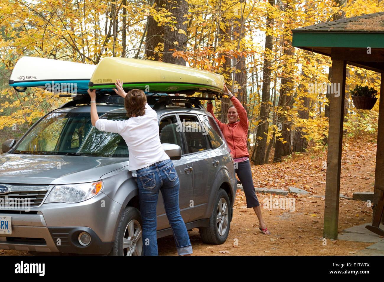 Dos jóvenes mujeres cargar los kayaks en el techo del vehículo, en casa de campo cerca de Oxtongue Lago Imagen De Stock