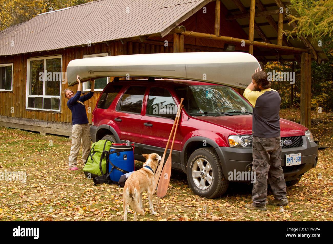 Pareja joven cargar canoa en el techo del vehículo, en casa de campo cerca de South River, Algonquin Park, Imagen De Stock