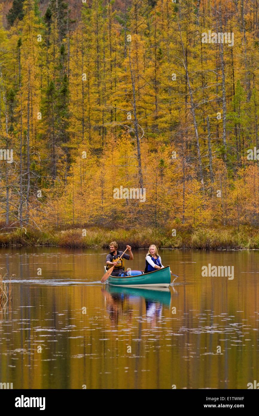 Pareja joven remar canoa en quietas aguas de pequeña cala en el extremo noroeste del parque Algonquin, Ontario, Imagen De Stock