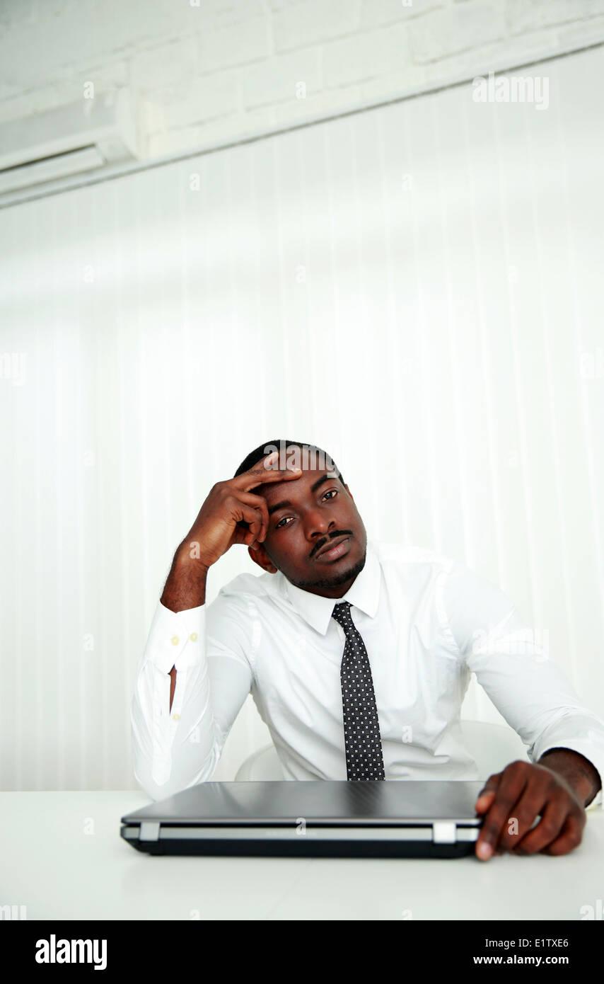 Empresario africano sentado en su lugar de trabajo en la oficina Imagen De Stock