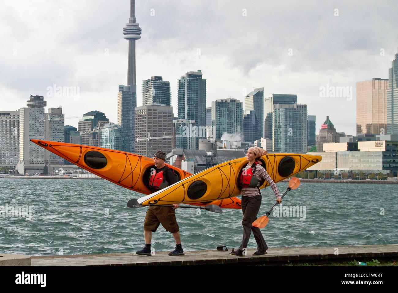 Pareja joven transportar kayaks desde el Lago Ontario, Toronto Waterfront, Toronto, Ontario, Canadá. Imagen De Stock