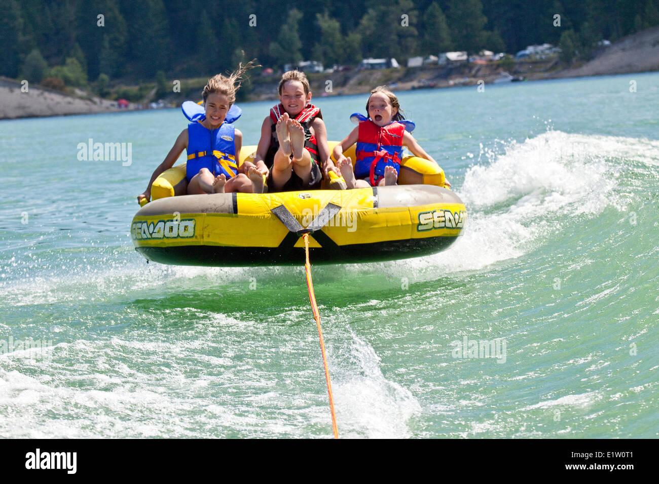 Tres niños disfrutan de los tubos en el Lago Koocanusa, East Kootenays, BC, Canadá. Imagen De Stock