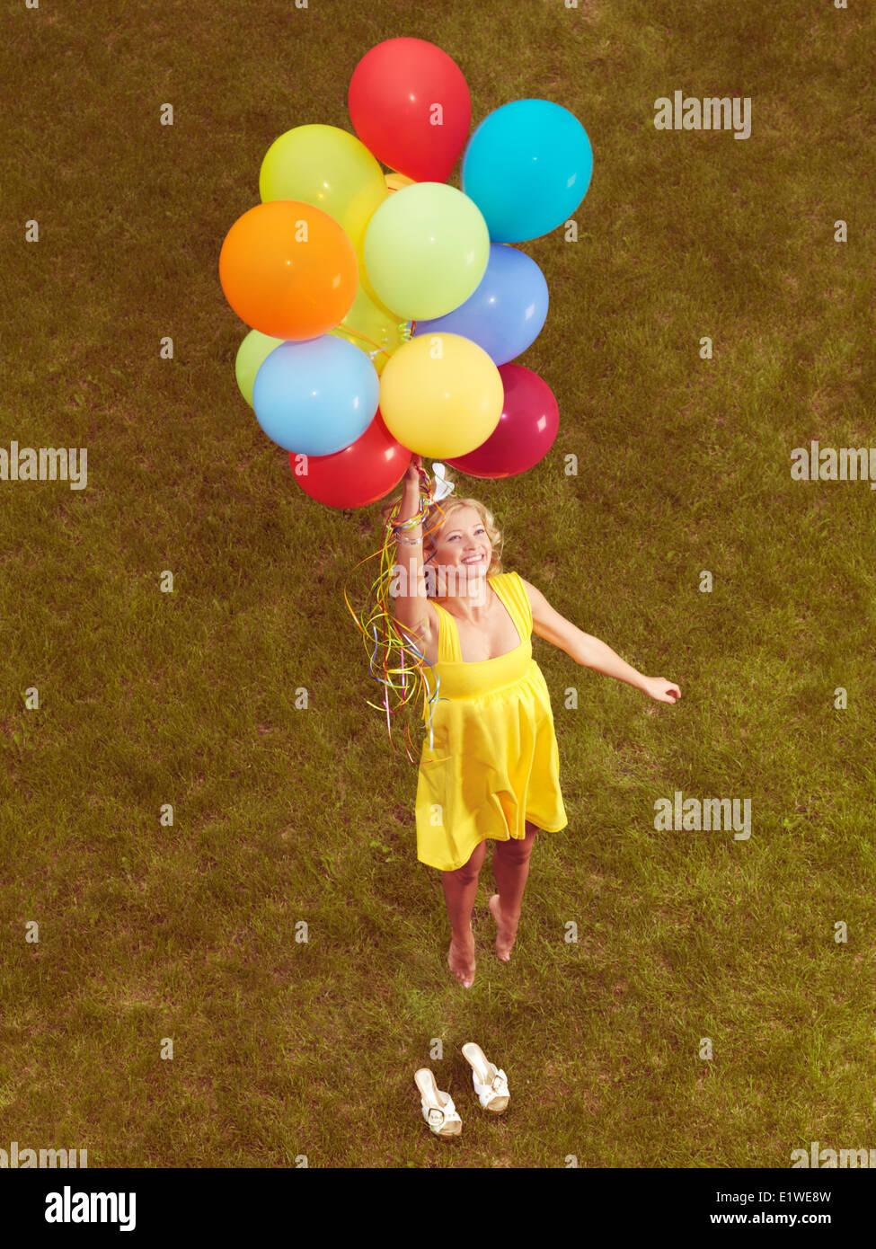 Feliz joven en amarillo vestido de verano volando desde el suelo con coloridos globos de helio, retro foto estilizados. Imagen De Stock