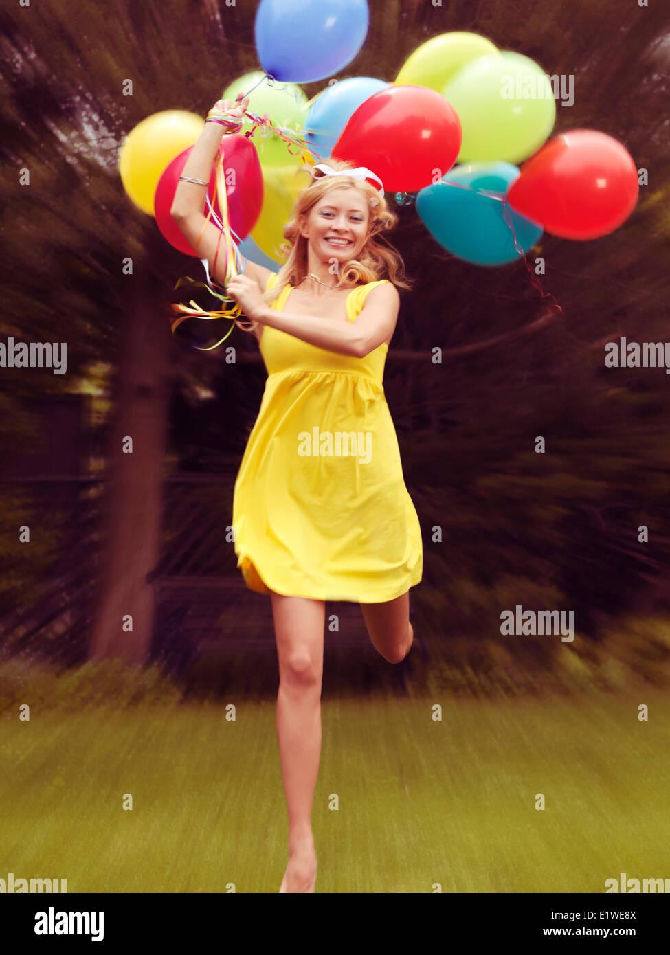 Feliz joven en ropa de verano corriendo con globos de colores Imagen De Stock