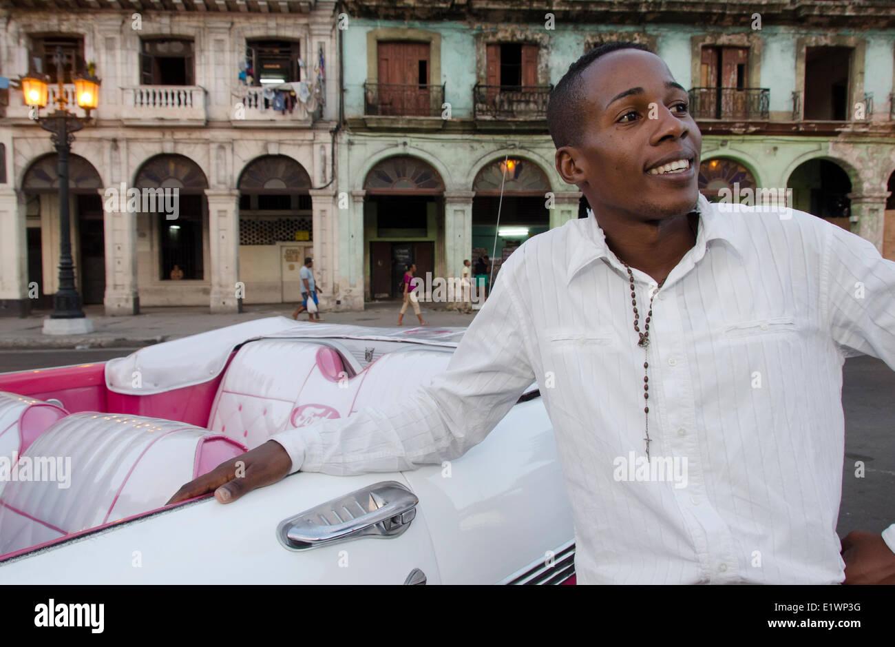 Joven cubano conductor y coche clásico americano y las fachadas de los edificios antiguos, La Habana, Cuba Imagen De Stock