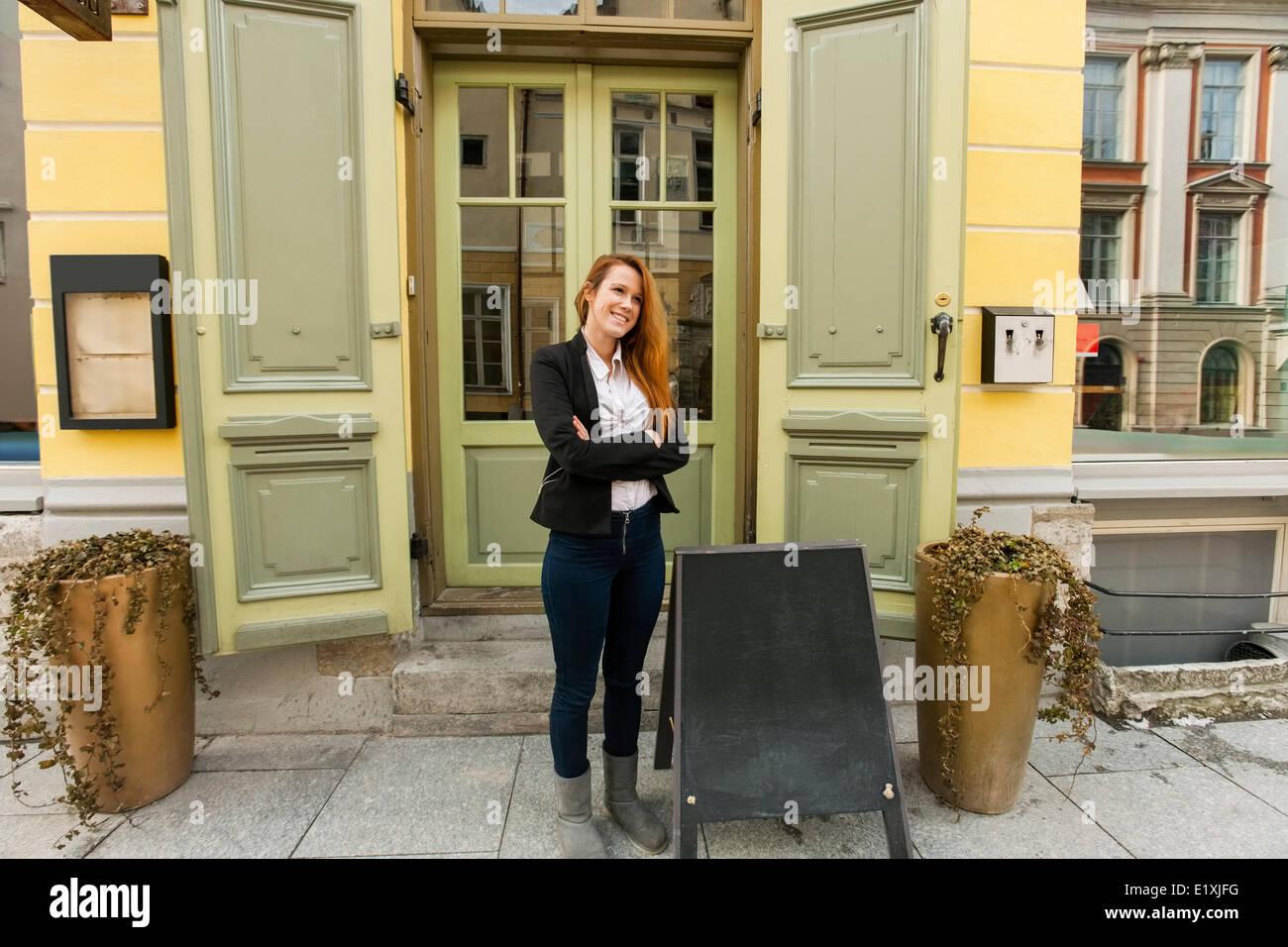 La longitud completa de la hembra de pie fuera propietario de restaurante Imagen De Stock