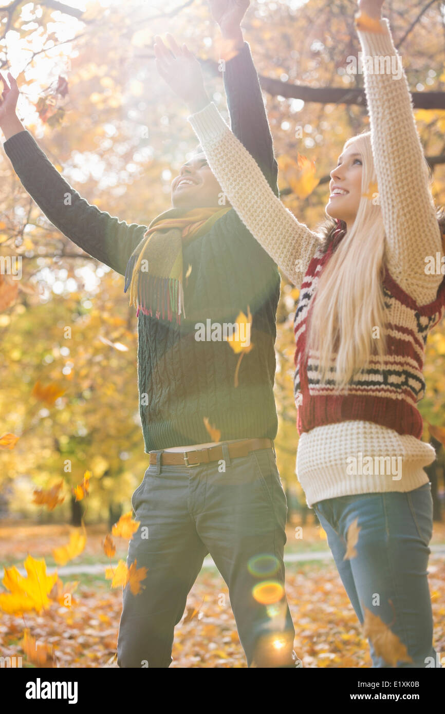 Feliz pareja joven con los brazos levantados disfrutando de caer hojas de otoño en el parque Imagen De Stock