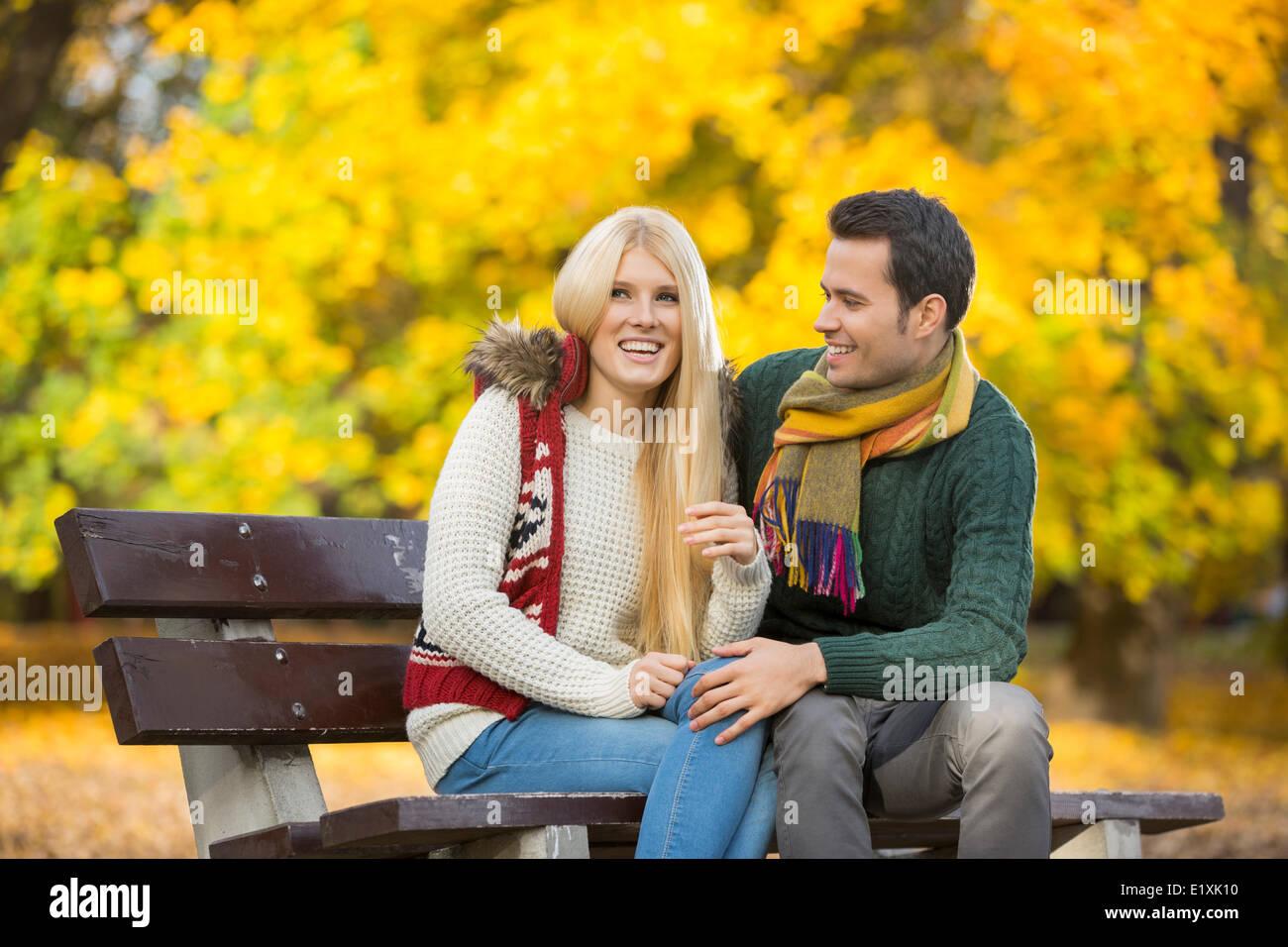 Joven pareja sentada en un banco del parque durante el otoño Foto de stock