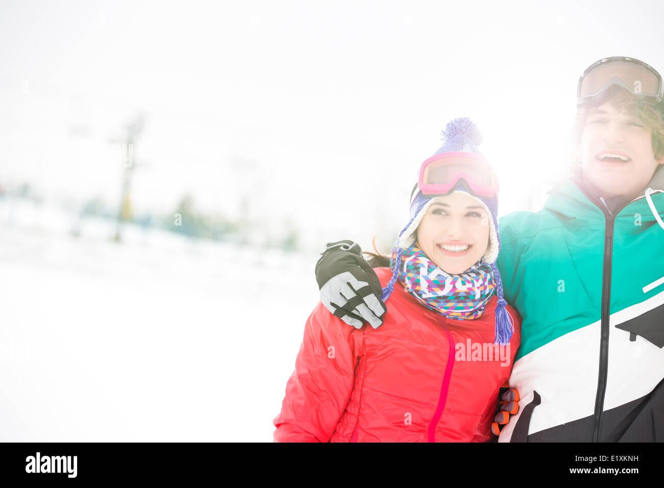 Pareja joven alegre de pie brazo alrededor en la nieve Imagen De Stock