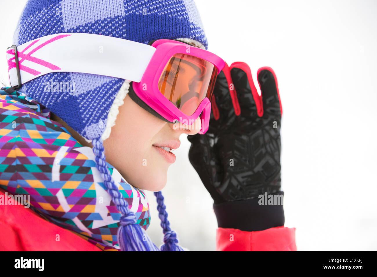 Vista lateral cerca de la hermosa joven en gafas de esquí mirando lejos Imagen De Stock