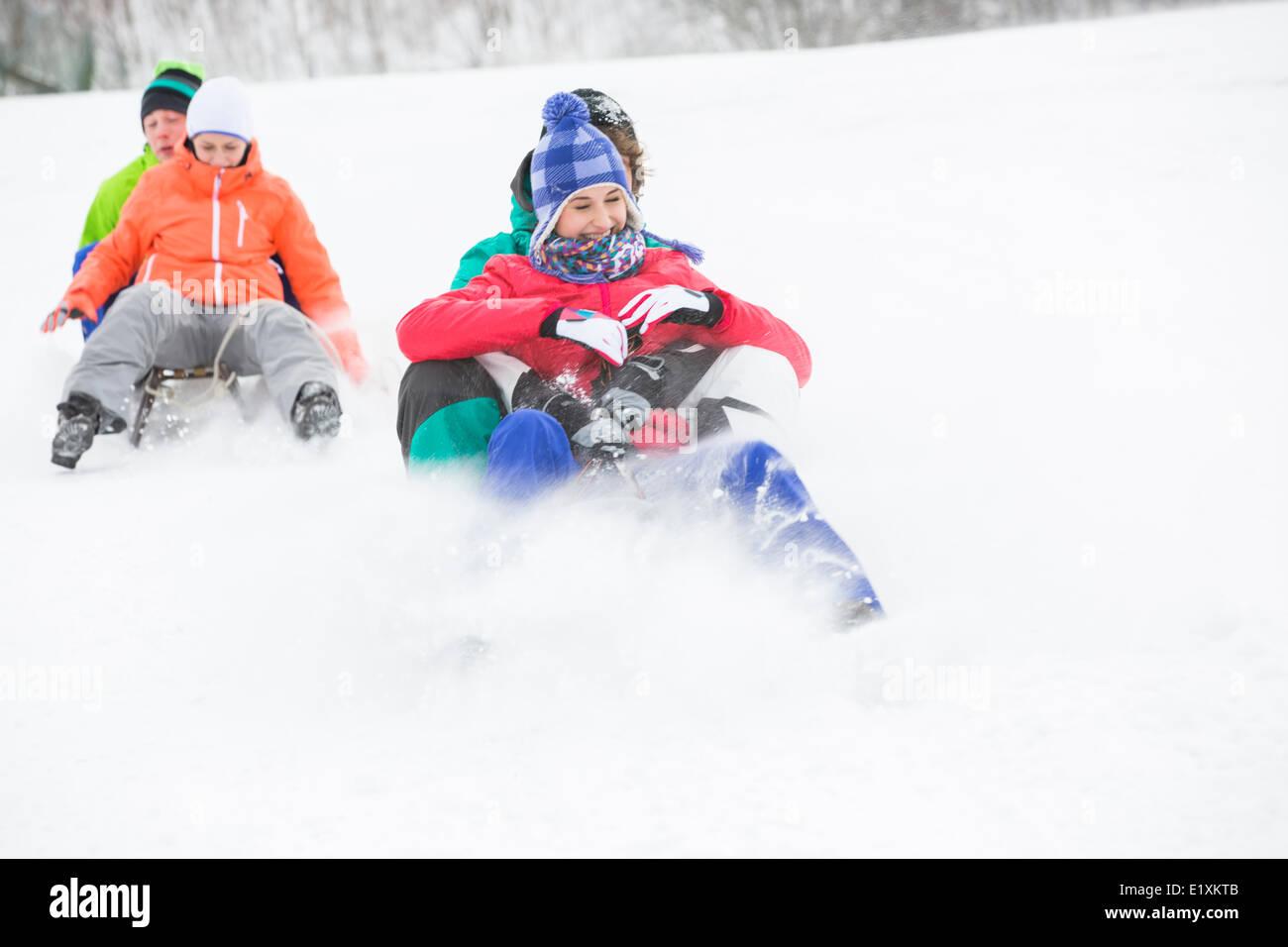 Las parejas jóvenes disfrutando de trineo sobre la nieve cubrió pendiente Foto de stock