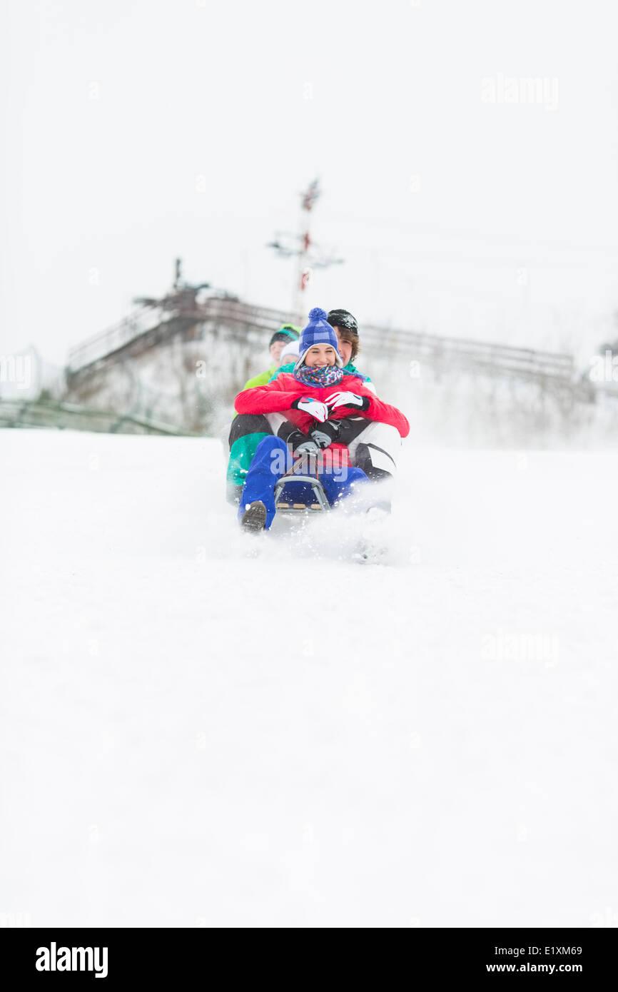 Grupo de amigos disfrutando de trineo en la nieve Imagen De Stock