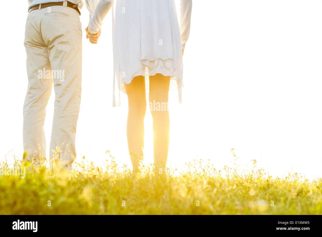Vista posterior de la parte media de la pareja tomados de las manos sobre el césped contra sky Imagen De Stock