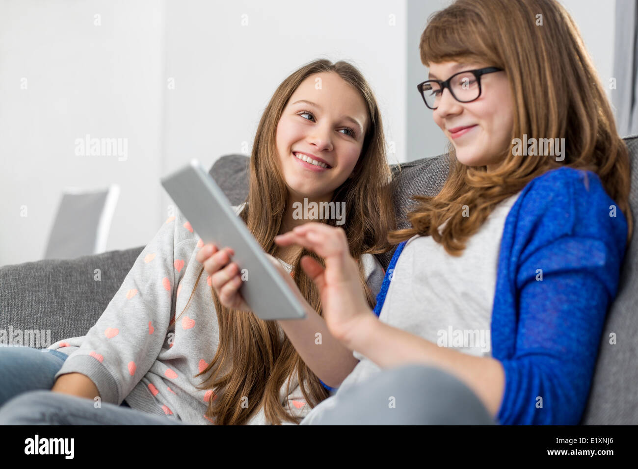 Feliz chica busca a la hermana utilizando tablet digital en el sofá en casa Imagen De Stock