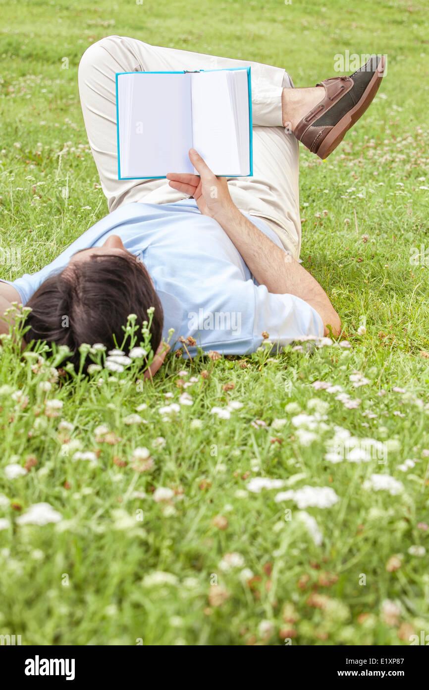 La longitud completa de la joven celebración libro tumbado sobre el césped en el parque Imagen De Stock