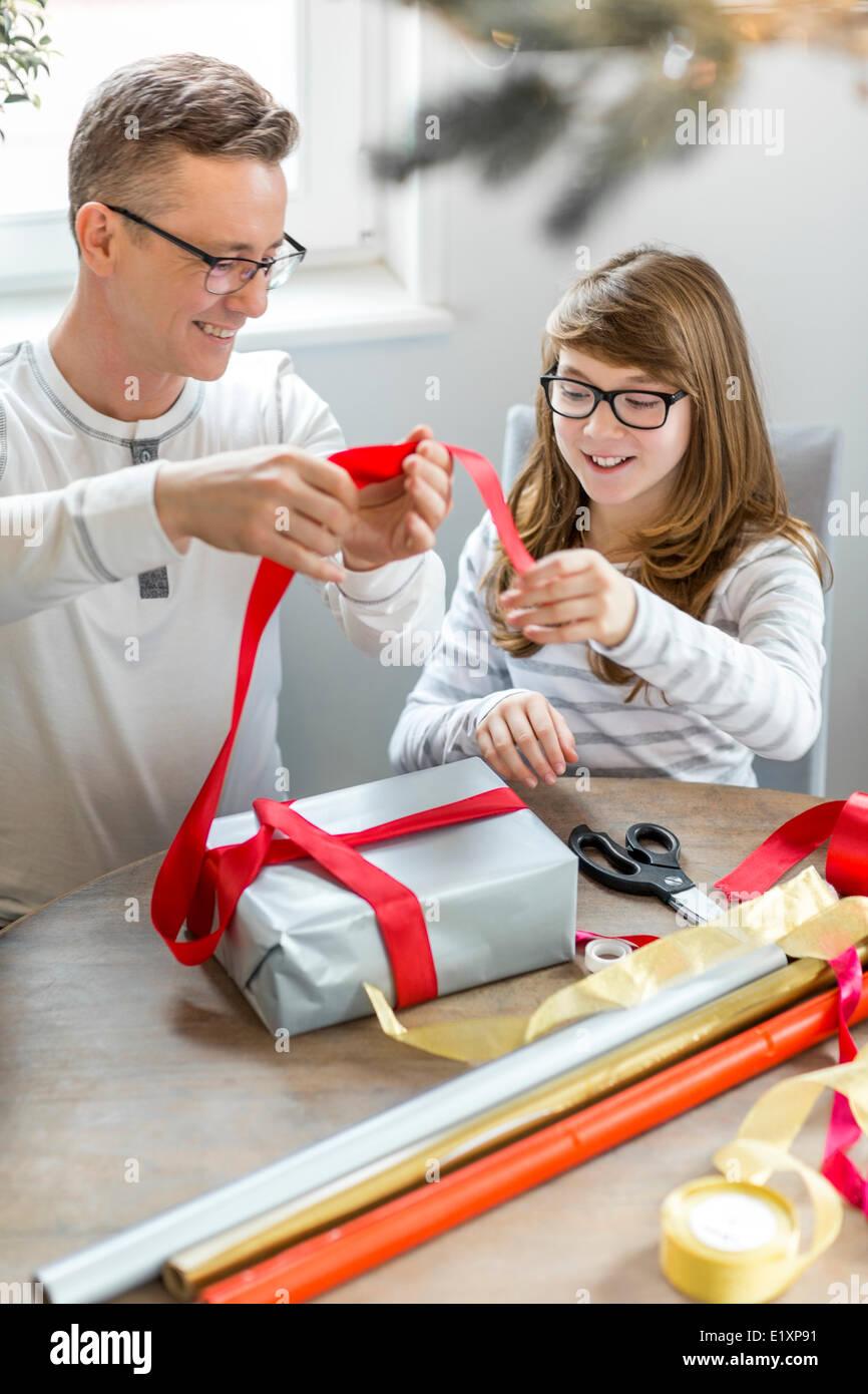 Padre e hija feliz navidad de encintado en casa Imagen De Stock