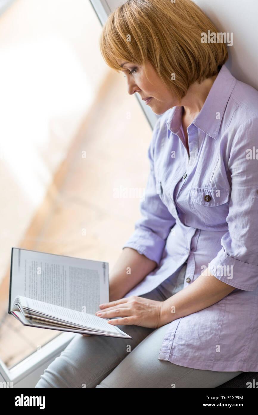 Mujer madura, libro de lectura mientras está sentado en la casa por la ventana Foto de stock