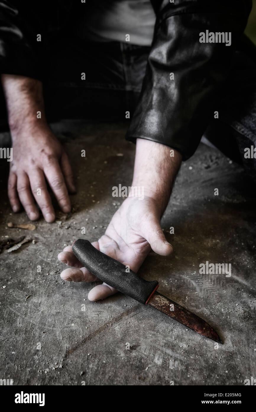 Las manos del hombre con una cuchilla vieja y oxidada Imagen De Stock