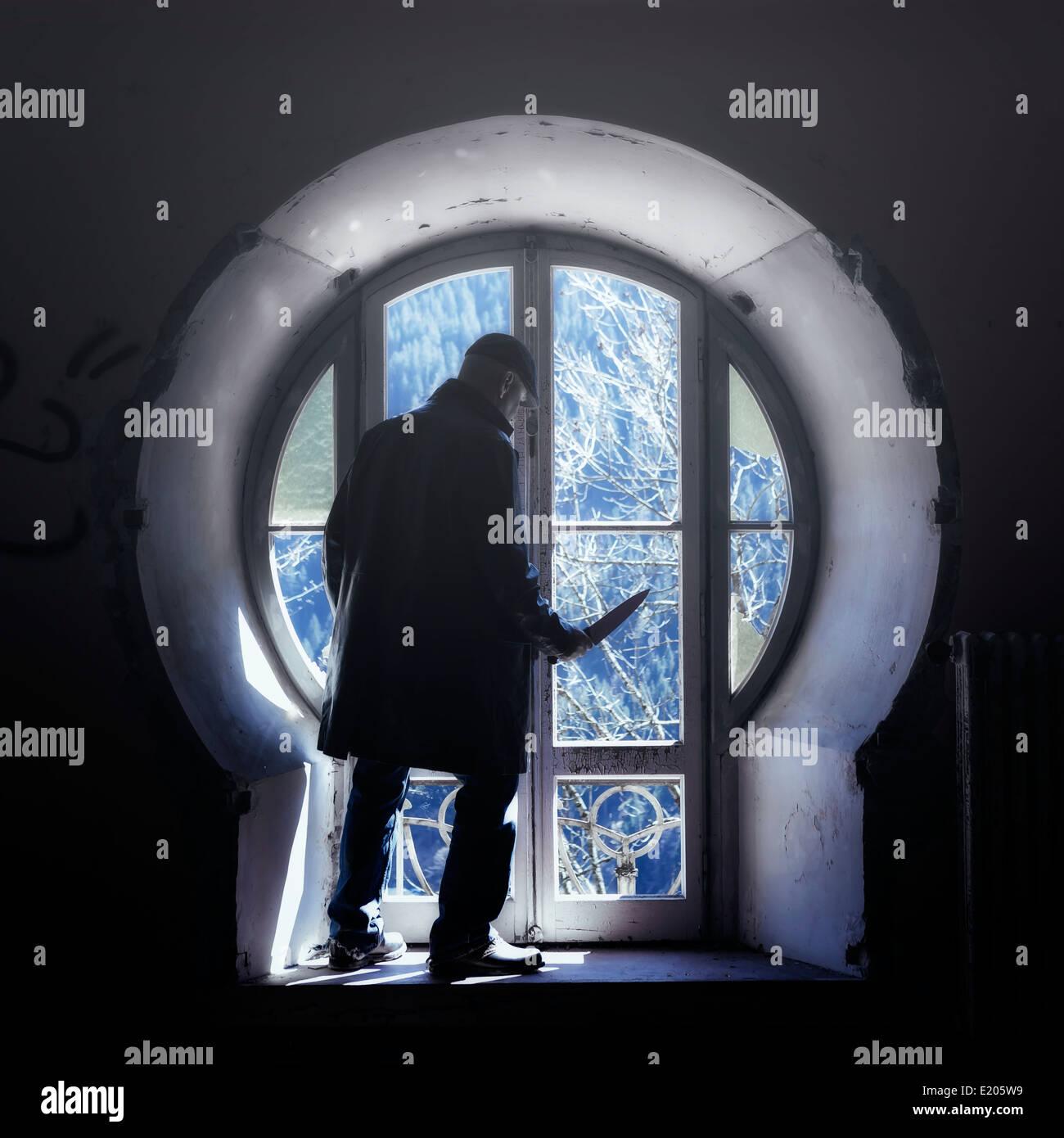 Un hombre con un cuchillo delante de una ventana de un viejo edificio abandonado Imagen De Stock