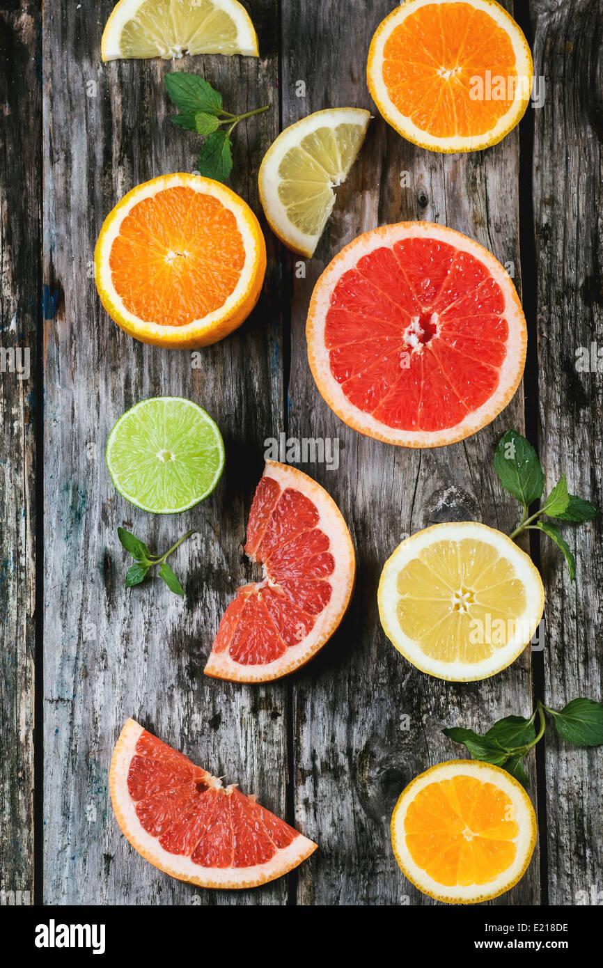 Conjunto de rodajas de cítricos limón, lima, naranja, pomelo con menta sobre fondo de madera. Vista desde arriba. Foto de stock